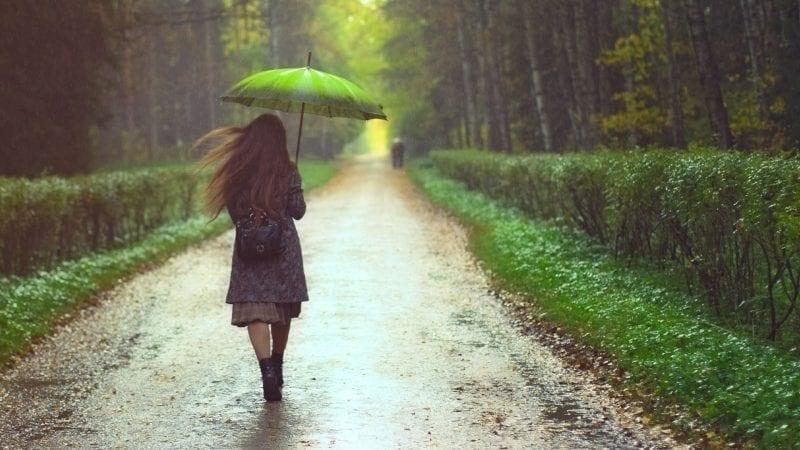 Eine Frau geht bei Regenwetter durch den Wald