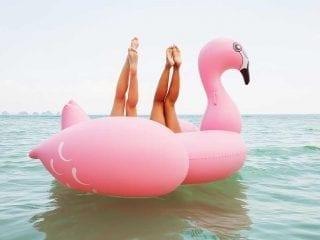 Vier Frauenbeine in einer Flamingoluftmatratze im Meer