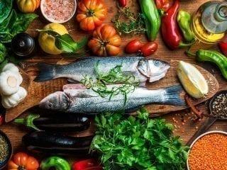 Gesunde Lebensmittel wie Fisch, Obst und Gemüse stilvoll präsentiert