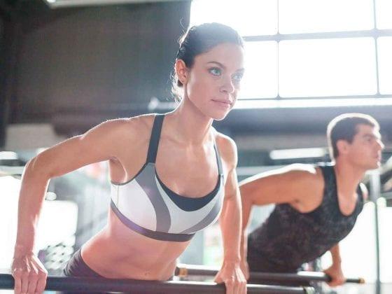 Eine Frau und ein Mann nutzen die Trainingsgeräte eines Fitnessstudios.