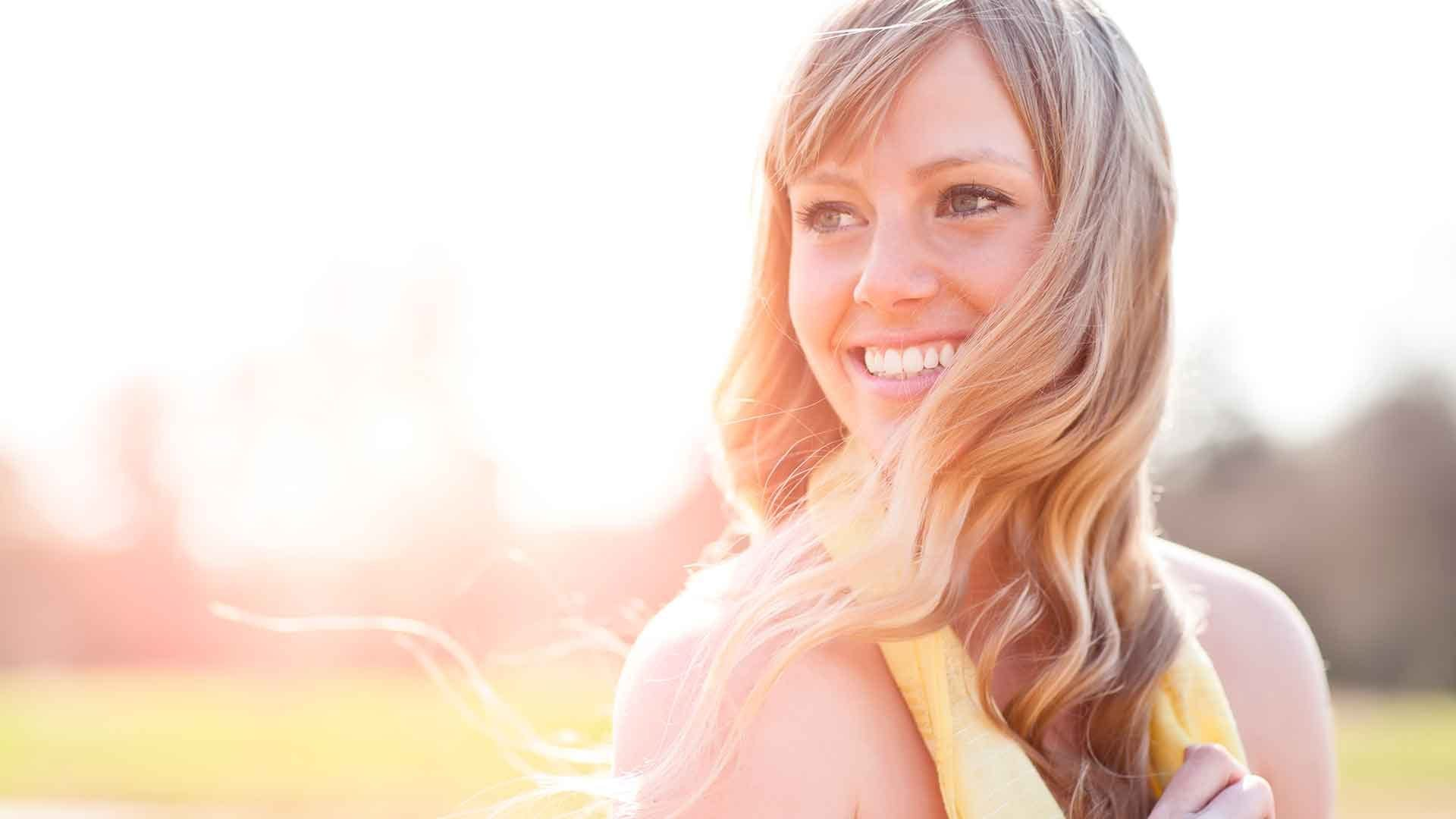 Blonde Frau im gelben Sommerkleid