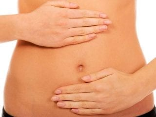 Frauenhände auf dem Bauch