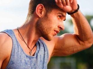 Sportlicher Mann hält sich die Hand an die Stirn