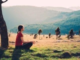 Eine Frau meditiert in der Natur