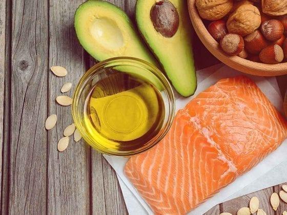 Roher Lachs, Avocado, Öl und Nüsse auf einer Holzunterlage