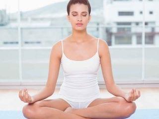 Eine Frau sitzt mit geschlossenen Augen im Lotussitz