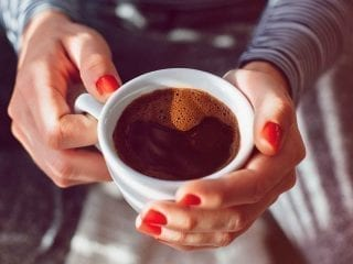 Frauenhaende und eine Tasse schwarzer Kaffee
