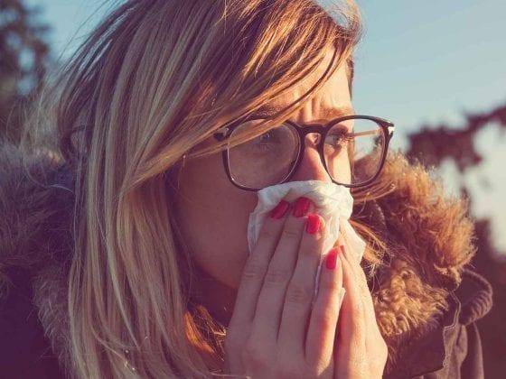 Eine junge Frau putzt sich die Nase