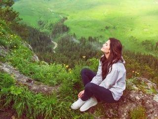 Frau auf einem Gipfel atmet tief durch