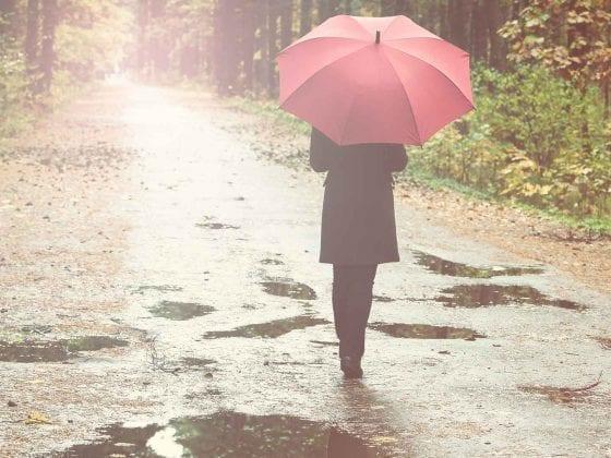 Frau bei Regenwetter mit Regenschirm
