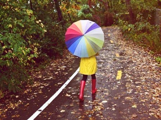 Junge Frau geschützt mit Regenmantel, Regenstiefeln und Regenschirm