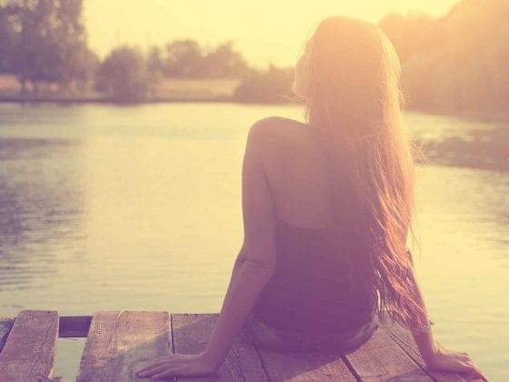 Eine junge Frau blickt auf den See