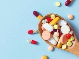 Ein Holzlöffel mit Tabletten und Kapseln gefüllt
