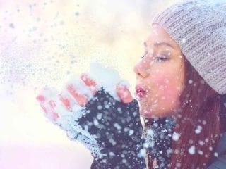 Eine Frau mit Pudelmütze in einer Schneelandschaft