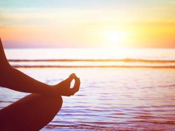 Eine Frau meditiert am Strand beim Sonnenaufgang
