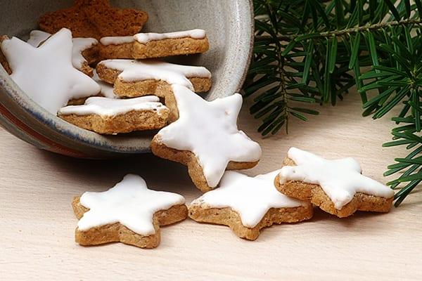 Neben einem Tannenzweig liegen Weihnachtsplätzchen in Sternform.