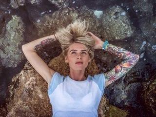 Junge Frau liegt am Wasser an einem Felsstrand