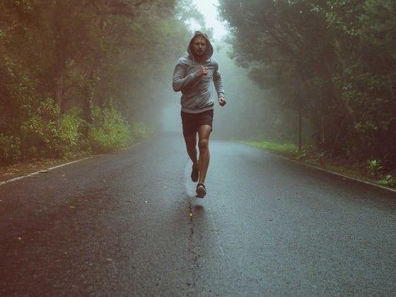 Ein Jogger läuft auf einer Waldstraße