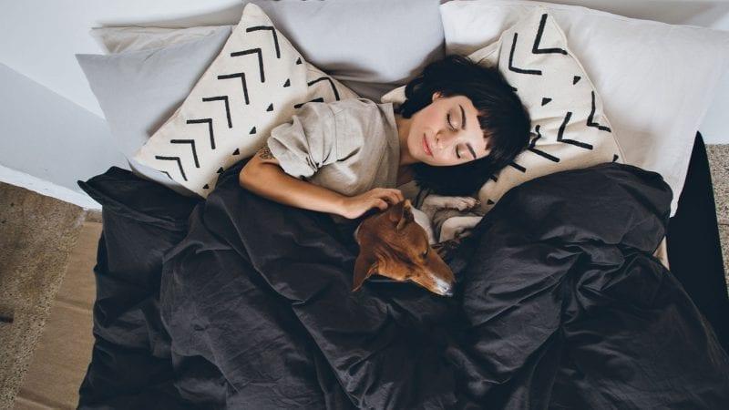 Junge Frau im Bett mit Hund
