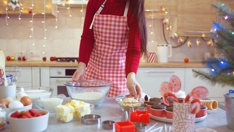 Eine Frau backt in einer Küche mit Weihnachtsdekoration