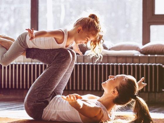 Ein junge Mutter mit Tochter bei einer Yogaübung