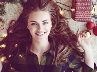 Eine junge Frau lächelt zu Weihnachten entspannt in die Kamera