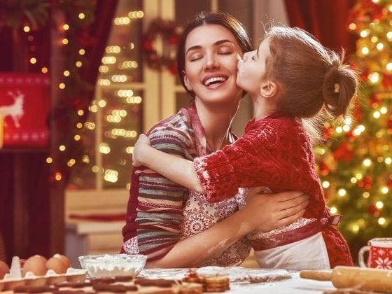 Kleine Tochter küsst Mutter zu Weihnachten