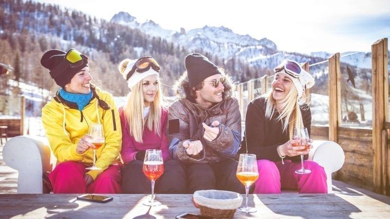 Skifahrerinnen sitzen in der Gruppe zusammen und trinken zusammen