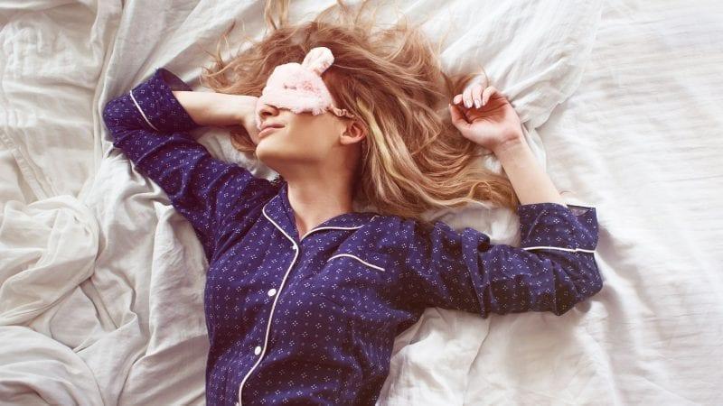 Eine Frau schläft im Bett mit einer Augenmaske