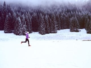 Joggerin läuft durch eine schneelandschaft