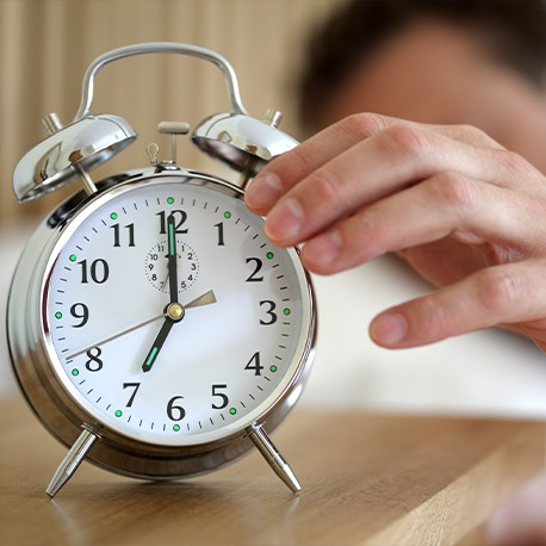 Ein silberner Wecker mit Ziffernblatt. Es ist sieben Uhr morgens.