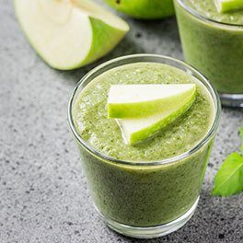 Ein grüner Smoothie mit Matcha und geschnittenen, grünen Apfelstücken als Dekoration