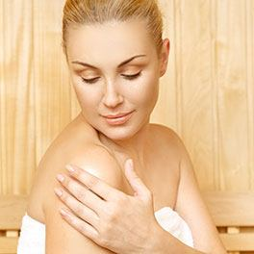 EIne blonde Frau reibt sich Sacha-Inchi-Öl auf den rechten Oberarm